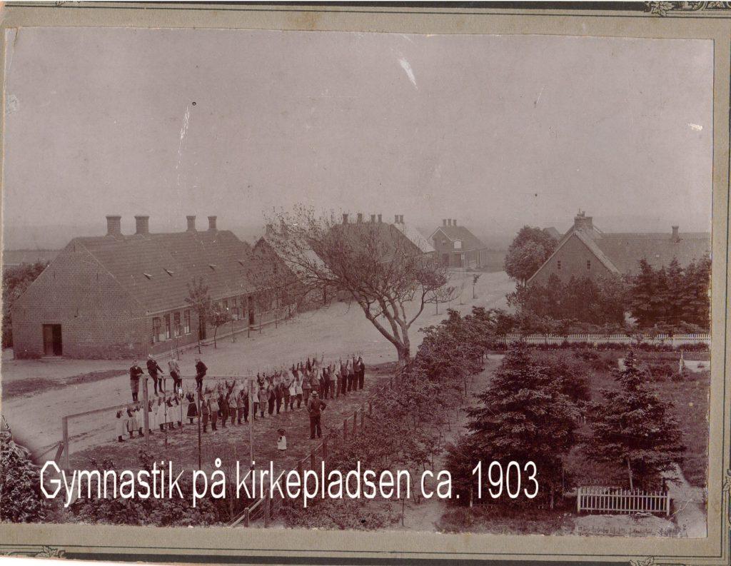Førstelærer Thomas Thomasen havde i 1895 gymnastik med eleverne. på kirrkepladsen umiddelbart ved siden af det gamle træ. Måske har det været en kdd omgang. På den anden side af vejen ligger den skole, som blev bygget iu 1840.