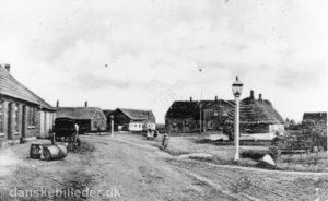 Sådan så kirkepladsen i Ørre ud i 1906. Man bemærker den markante gaslampe og bagved ligger skolen, som nu er kirkehus. Til højre ses noget af kirken. I gården til venstre i billedet boede den navnkundige skolelærer og foregangsmand Iver Holmgaard.
